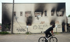 A man rides a bicycle past a burned out building Friday after a night of protests and violence in Minneapolis, Minnesota.