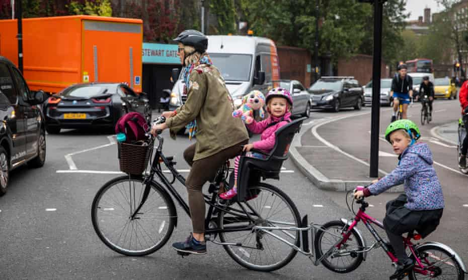 Family cycling to school in rush hour. Children suffer from high levels of pollution on London's roads.