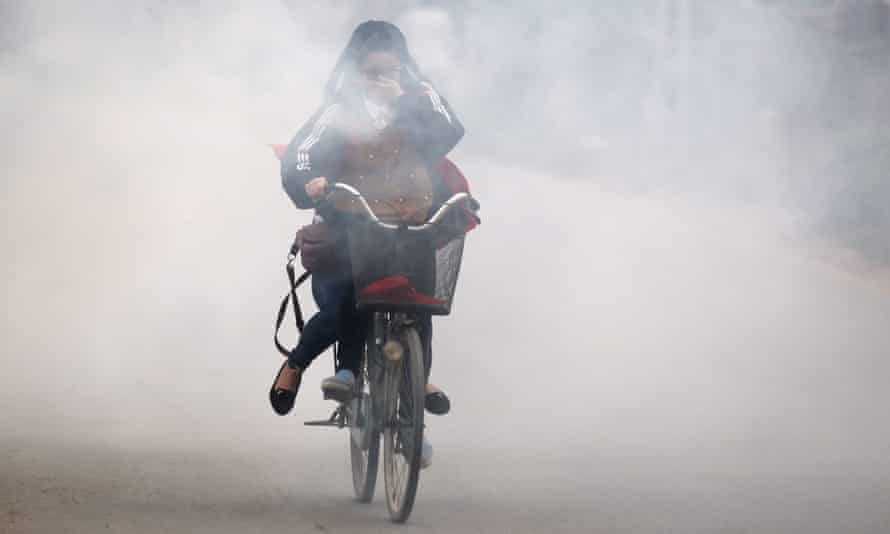 A girl covers her face as she cycles past smoke created by burning waste materials in a street in Hanoi.