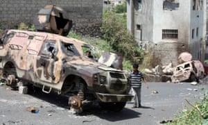 A boy walks past a damaged armoured vehicle in Yemen.