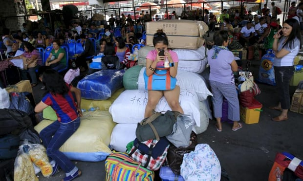 Stranded passengers guard their belongings while waiting at a bus terminal in Manila