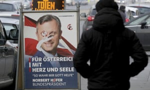 A person passes a poster of Norbert Hofer.