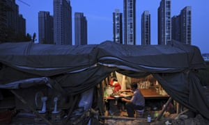 A labourer having his dinner under his shed at a construction site of a residential complex in Hefei