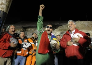 The last miner to be rescued, Luis Urzua, gestures next to Chile's president, Sebastián Piñera, after his rescue from the collapsed San José gold and copper mine, where he had been trapped for 70 days. Thirty-three trapped miners were hauled up in a cage through a narrow hole drilled through 2,000 ft of rock. 13 October 2010