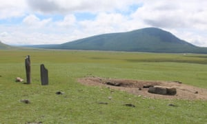 "A looter's pit sits beside two Bronze Age ""deer stone"" monuments at Khorigiin Am, Mongolia."