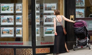 Woman with pushchair looking at houses in estate agent window