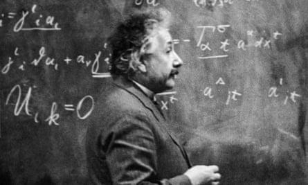 German-born physicist Albert Einstein (1879 - 1955) standing beside a blackboard with chalk-marked mathematical calculations written across it.