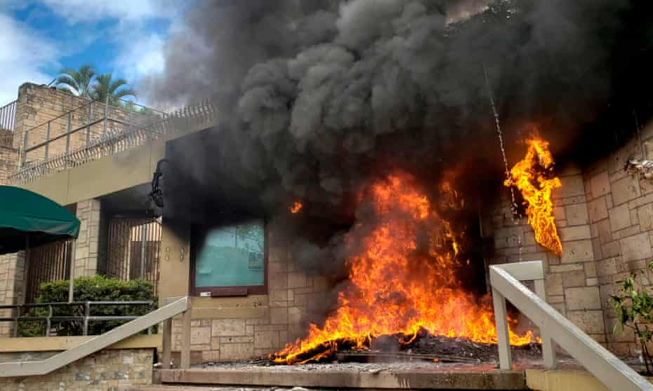 The entrance of the US embassy in Tegucigalpa burns after being set on fire by demonstrators of the education and health sectors protesting against government reforms, on 31 May.