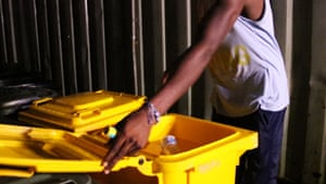 Men store water in bins at the Manus Island detention centre.