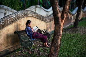 A female guest reads a book in the garden at Dhara Dhevi Hotel, Chiang Mai, Thailand