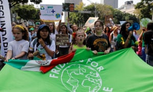 People hold a flag as they take part in a Global Climate Strike rally in Mexico City