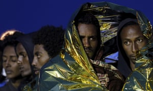 Migrants wrapped in thermal blankets queue to disembark from a rescue vessel in the Sicilian harbour of Augusta, Italy.