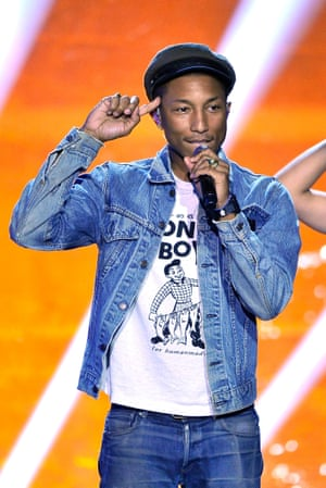 Pharrell Williams is behind Clinton.