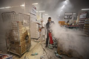 Employees douse a fire started by protesters inside a Carrefour supermarket during a protest against the murder of Black man Joao Alberto Silveira Freitas on Brazil's National Black Consciousness Day.