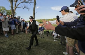Phil Mickelson greets fans as he walks up to the 18th tee.