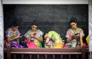 Bangkok, Thailand: dancers in traditional costumes rest during a heavy downpour at Erawan shrine