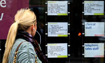 A woman examines job notices at a recruitment agency