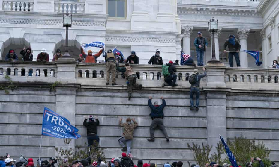 A mob of Trump supporters climb the west wall of the the US Capitol in Washington.