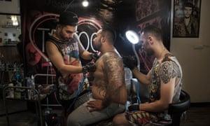 Tattoo artist Mohammed works in his backroom studio in south Tehran.