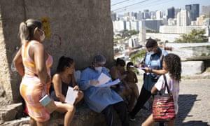 A city health worker waits for the results of a resident's quick Covid-19 test at Morro da Providencia favela, Rio de Janeiro, Brazil, 3 September 2020.