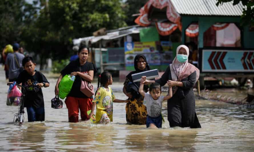People carry their belongings as they wade through flood water in Pebayuran, West Java, Indonesia