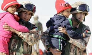 Jordanian security forces help refugee girls after crossing from Syria into Jordan