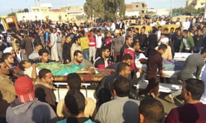 Injured people are evacuated from the scene of a militant attack on al-Rawdah mosque in the northern Sinai peninsula of Egypt on Friday