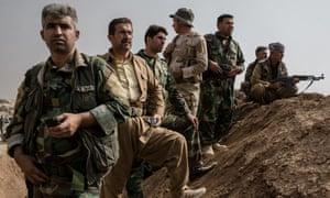 Peshmerga fighters stand on an earthen berm near Bashiqa