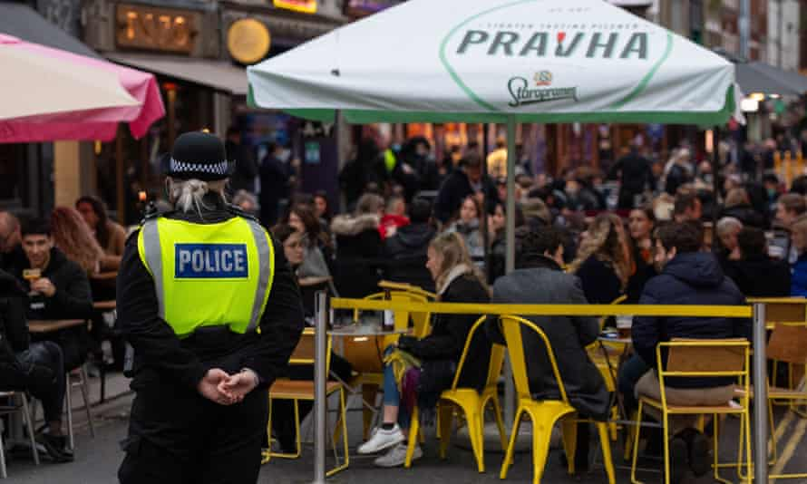 Officers monitor people seated outside bars and restaurants in Soho, London, last weekend.