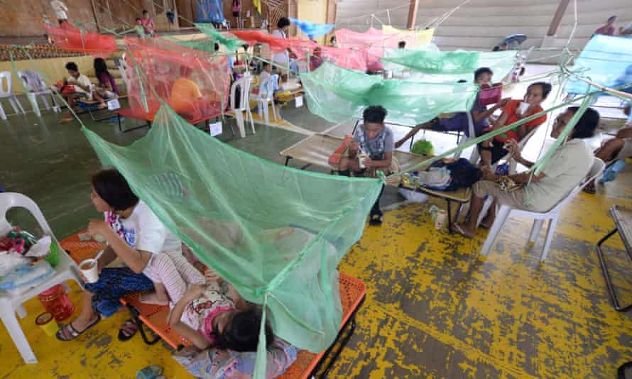 Mosquito nets cover beds at a makeshift medical facility inside a gym in the town of Maasin, in Iloilo province, during a 2019 outbreaak of dengue fever in the Philippines