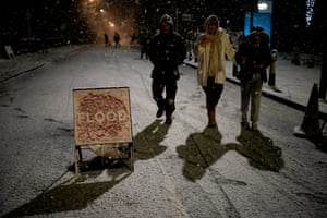 People walk past snow-covered flood warning signs in Didsbury, Manchester, as people were warned to evacuate their homes