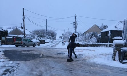 People shovelling snow and dislodging ice outside the Jamaica Inn, where more than 100 people sought refuge overnight after heavy snowfall hit the A30