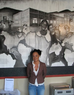 Dolezal, in 2009, standing in front of a mural she painted at the offices of the Human Rights Education Institute in Idaho