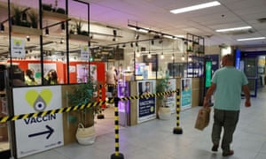 A shopper walks past a sign for a coronavirus disease vaccination centre installed inside a supermarket in Brussels.
