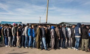 A queue for clothing at the migrant camp in Calais known as the 'Jungle' is seen in October 2015.