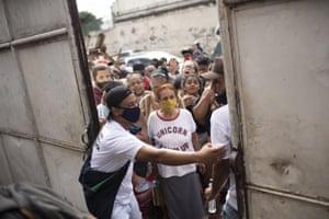 Residents gather outside a gate to receive donated food in the Jacarezinho favela of Rio de Janeiro, Brazil
