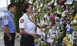 Miami-Dade Fire Rescue personnel Fai Yeung and Chief Melanie C. Adams visit the makeshift memorial setup near the partially collapsed 12-story Champlain Towers South Condo.