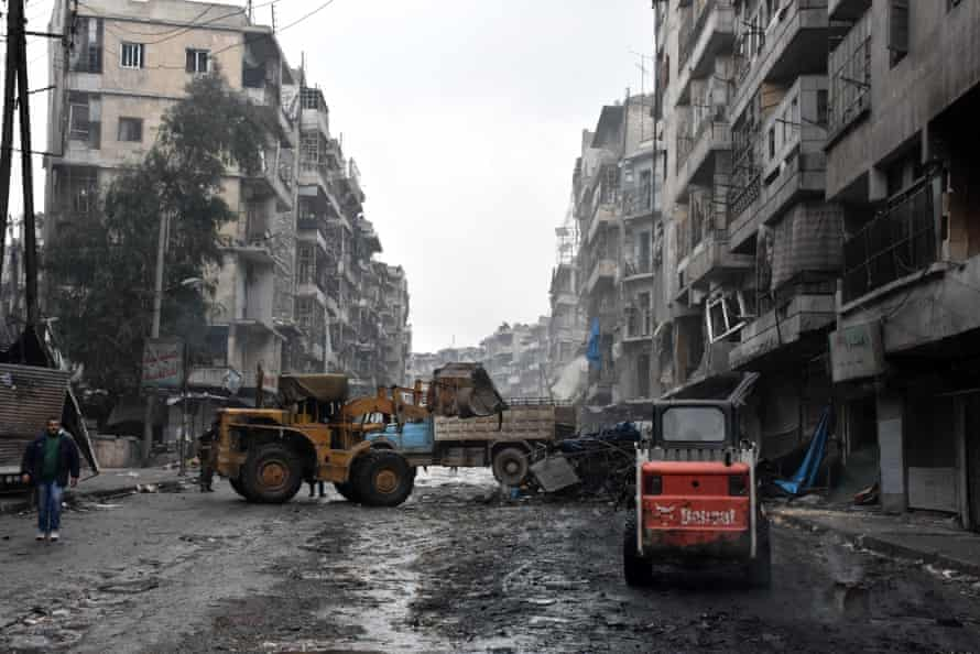 A tractor removes rubble as the Syrian government starts to clean up areas formerly held by opposition forces in the northern city of Aleppo.
