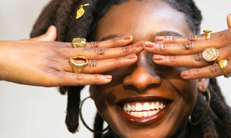 Little Simz with big gold rings and fingers over her eyes, smiling