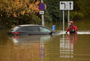A member of the fire and rescue service wades through flood water as he passes an abandoned car in Rotherham.