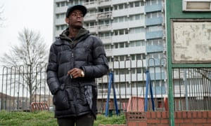 Micheal Ward in Blue Story standing in a puffa jacket and cap outside high rise flats