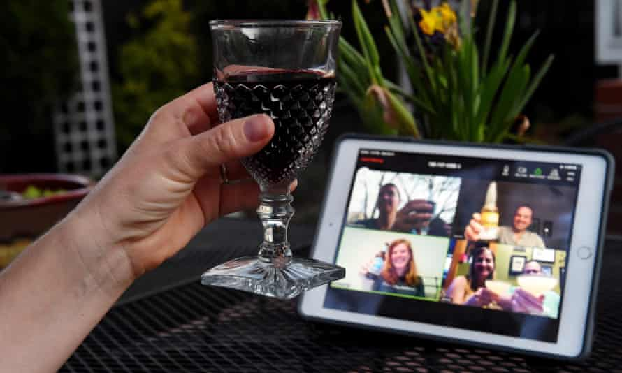 A woman lifts her glass and cheers with friends during a virtual happy hour amid the coronavirus  crisis