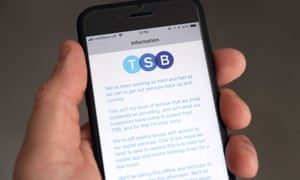 A customer using the TSB online banking app on a smartphone reads a message apologising for IT issues that left customers unable to access their money