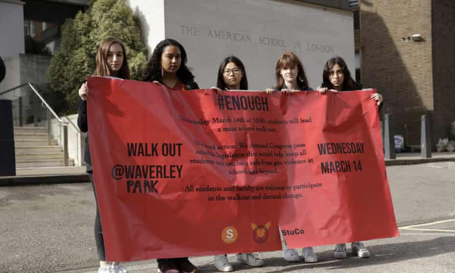 Students with a banner outside the front of the American School in London, after taking part in a 10am local-time, 17-minute walkout in the school playground, which was attended by approximately 300 students on Wednesday.