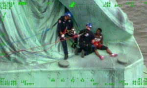 Patricia Okoumou is apprehended by police at the feet of Lady Liberty.