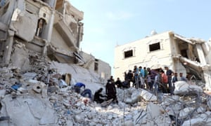 Syrian civil defence members and civilians search for survivors under the rubble of a site hit by airstrikes in the town of Kafr Takharim.