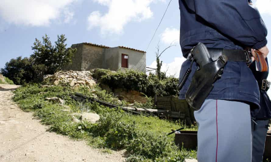 A policeman stands in front the house where a mafia boss was arrested in Sicily, Italy.