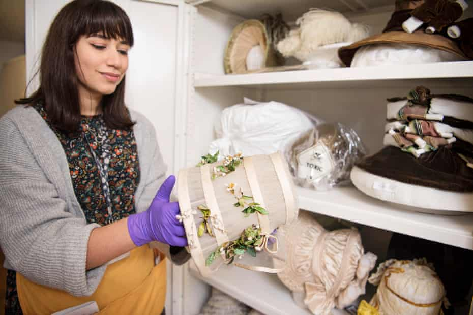 Ruby Hodgson holds a wedding bonnet from 1845 with leaves that might have been dyed with arsenic.
