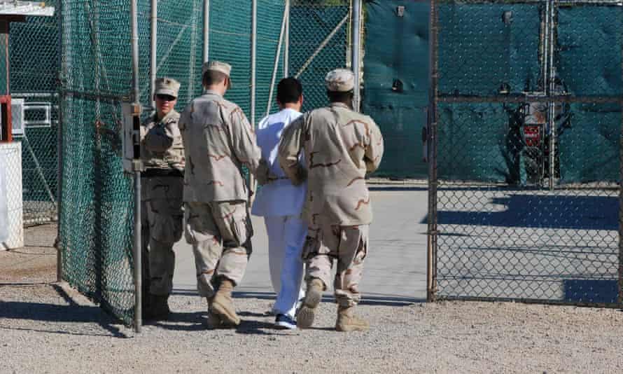 Navy guards escort a detainee through Camp Delta at Guantánamo Bay naval base.