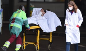 A patient is wheeled into La Paz hospital in Madrid.